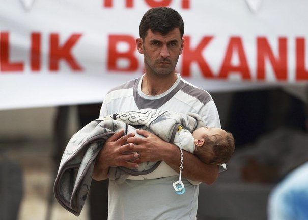 Man carrying a baby enters a medical tent at refugee camp for Syrian refugees in the Turkish border town of Yayladagi