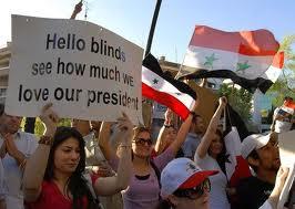 """La pancarte que brandit cette manifestante pro-Assad dit : """"Hello les aveugles, voyez comme nous aimons notre président"""""""