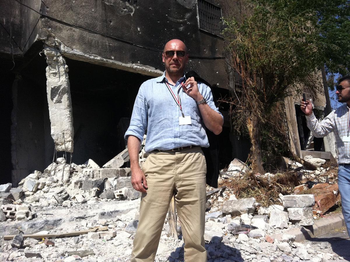 Alain Soral devant les ruines du commissariat incendié de Hama