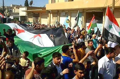 Manifestants anti-Bachar le 7 octobre : les contradictions et ambiguïtés de l'opposition résumées par trois drapeaux : l'officiel, celui de l'opposition et celui des Kurdes !