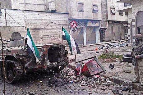 """Une bonne image """"de synthèse"""" de la confusion - tant militaire que médiatique - engendrée par la situation à Homs : le blindé détruit est décoré de drapeaux de l'opposition, et le militaire à côté est présenté comme un """"rebelle"""". Mais il pourrait tout aussi bien s'agir d'un blindé opposant détruit, et d'un soldat régulier..."""