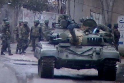 """Un point de contrôle de l'armée dans la banlieue de Damas : le gouvernement syrien a préféré prendre le risque d'un regain de tension internationale plutôt que celui d'une nouvelle """"bab-amrisation"""" des villes de Syrie"""